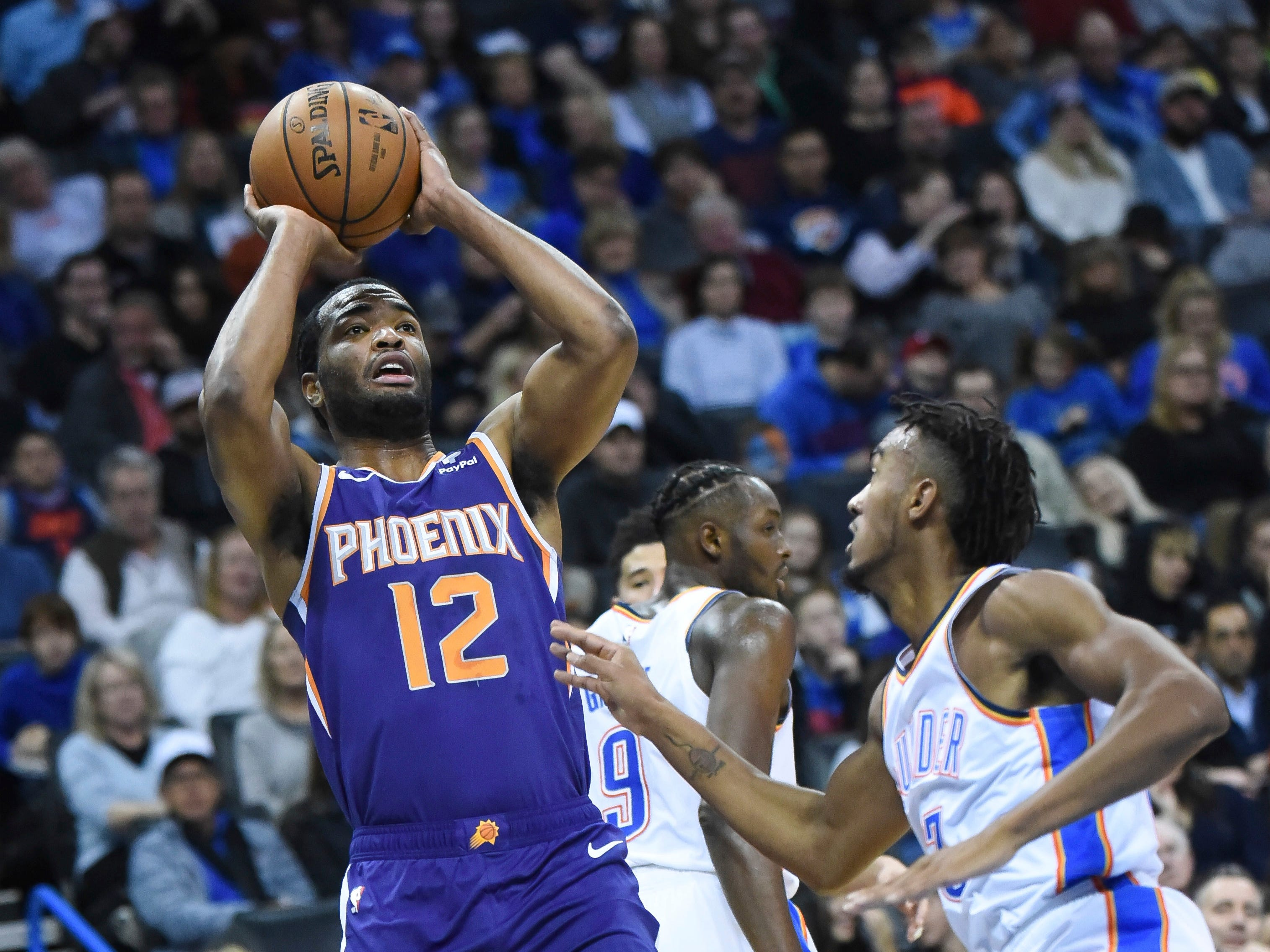 Phoenix Suns forward T.J. Warren (12) shoots the ball over Oklahoma City Thunder center Nerlens Noel (3) in the first half of an NBA basketball game in Oklahoma City, Monday, Nov. 12, 2018. (AP Photo/Kyle Phillips)