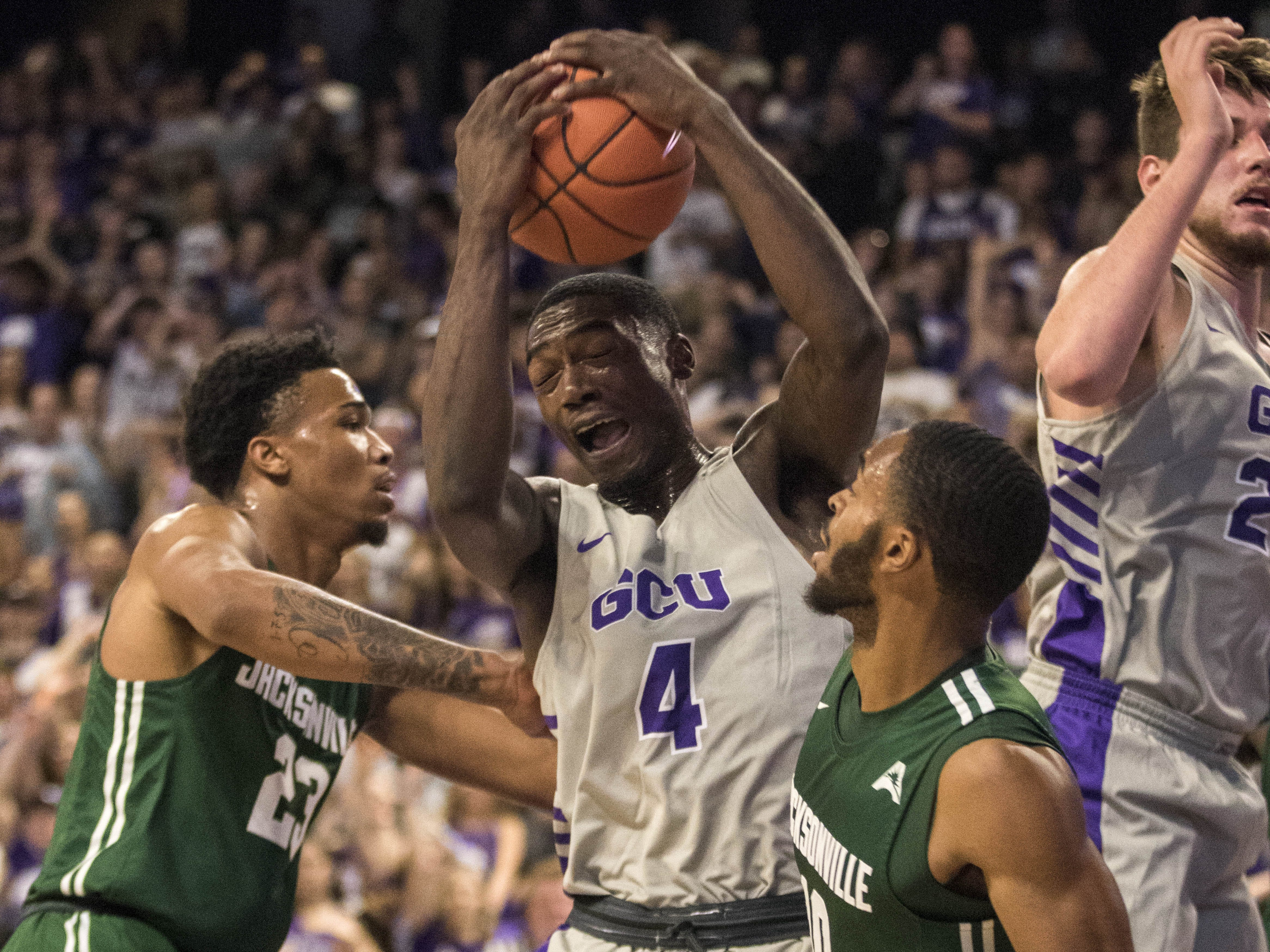 Grand Canyon University's Oscar Frayer (4) grimmaces as he pulls down a rebound against Jacksonville's Tyreese Davis (23) and Aamahne Santos (10) during the first half of their game in Phoenix, Monday, Nov.11,  2018.