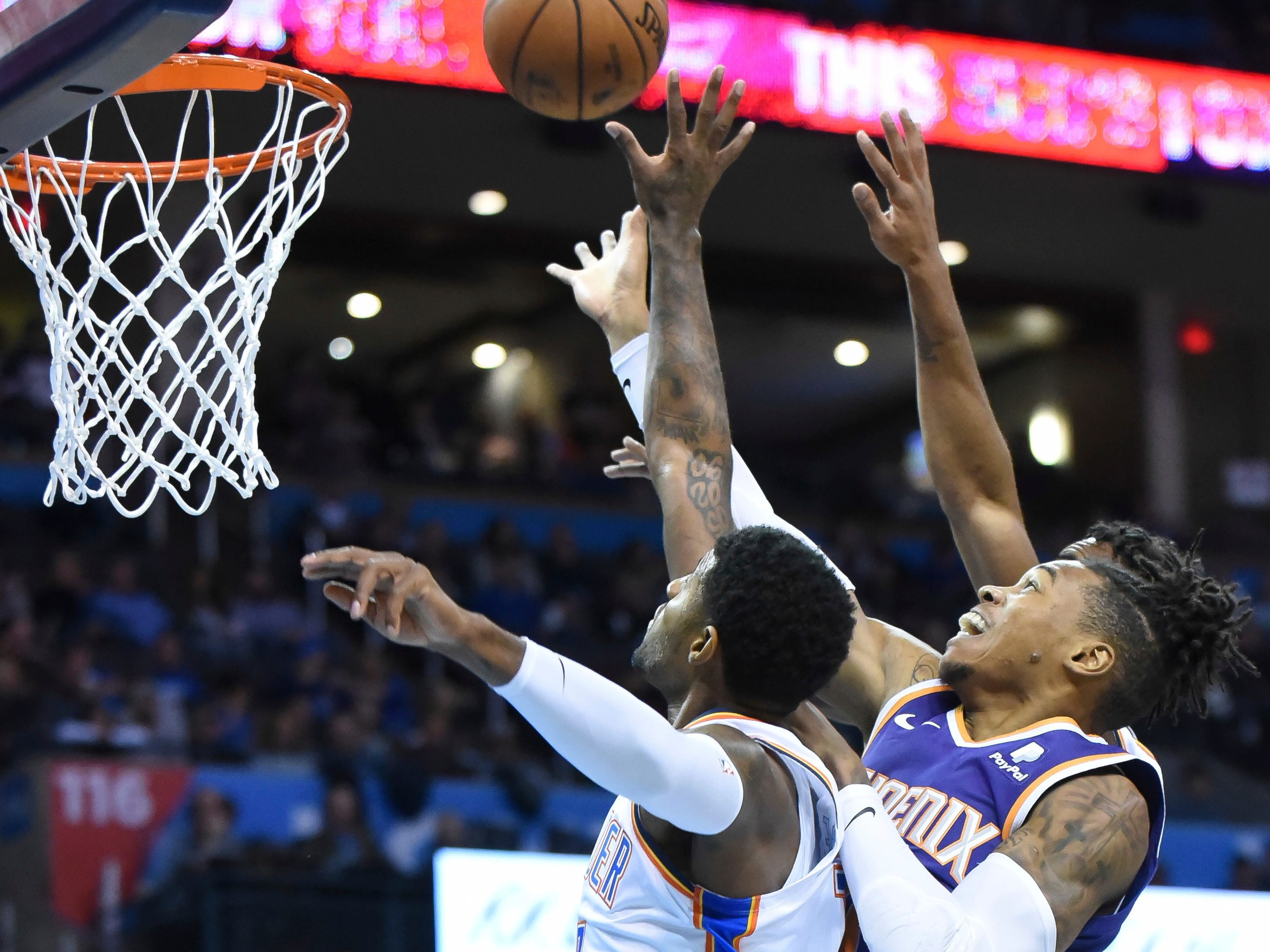 Oklahoma City Thunder forward Paul George, left, tries to beat Phoenix Suns forward Richaun Holmes, right to the rebound in the first half of an NBA basketball game in Oklahoma City, Monday, Nov. 12, 2018. (AP Photo/Kyle Phillips)