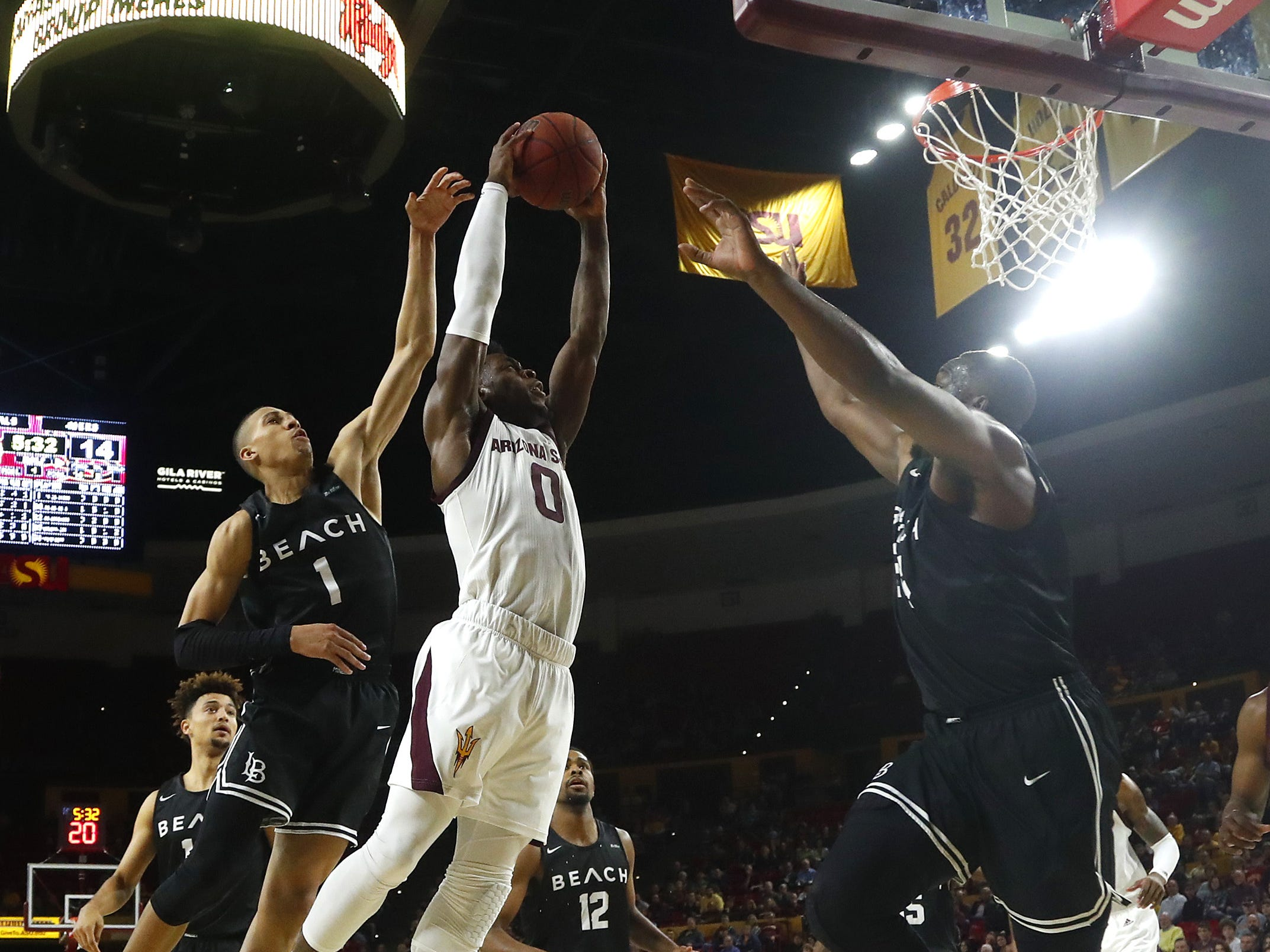 Arizona State's Luguentz Dort (0) shoots against Long Beach State's Ron Freeman (1) during the first half at Wells Fargo Arena in Tempe, Ariz. on November 12, 2018.