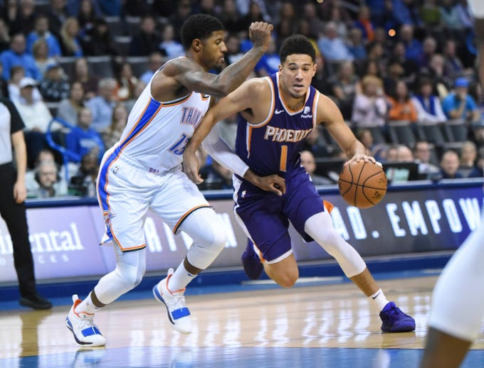 Phoenix Suns guard Devin Booker (1) drives past Oklahoma City Thunder forward Paul George (13) in the first half of an NBA basketball game in Oklahoma City, Monday, Nov. 12, 2018. (AP Photo/Kyle Phillips)