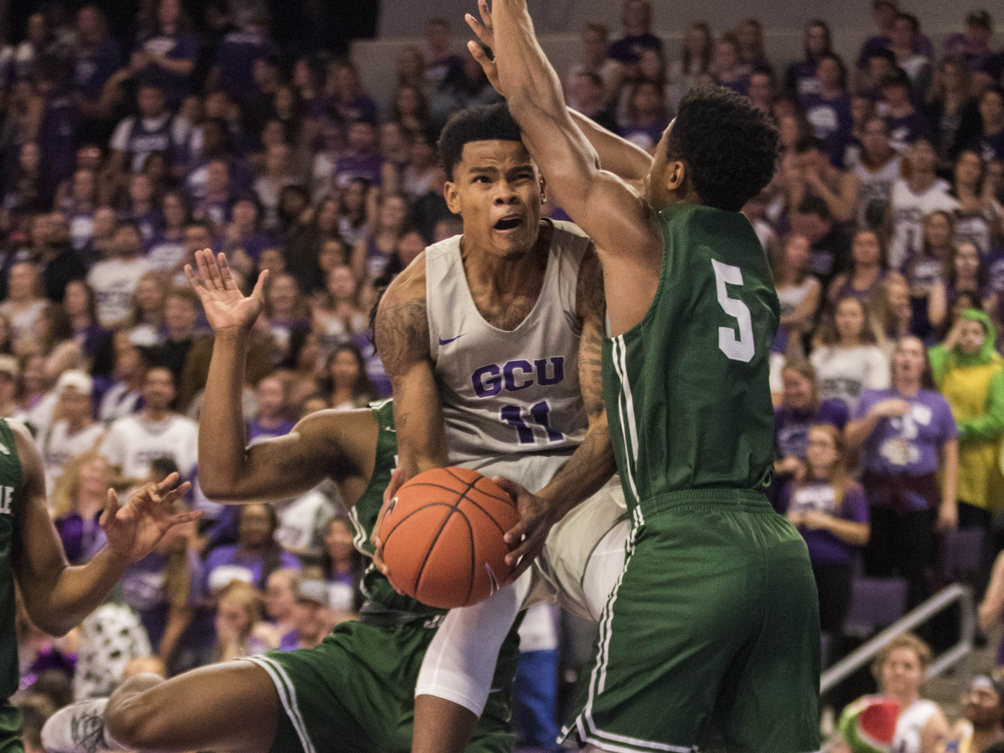 Grand Canyon University's Damari Milstead (11) drives to the basket against Jacksonville's DeAnthony McCallum (5) and Aamahne Santos (10) during the first half of their game in Phoenix, Monday, Nov.11,  2018.