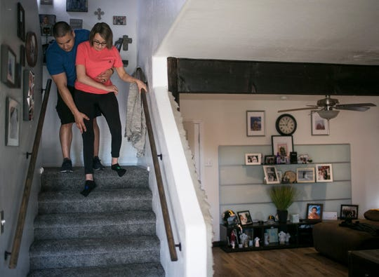 Frank Calzadillas his wife, Jovanna, go down the stairs of their home as they get ready to go to physical therapy. Jovanna attends physical therapy four days a week.