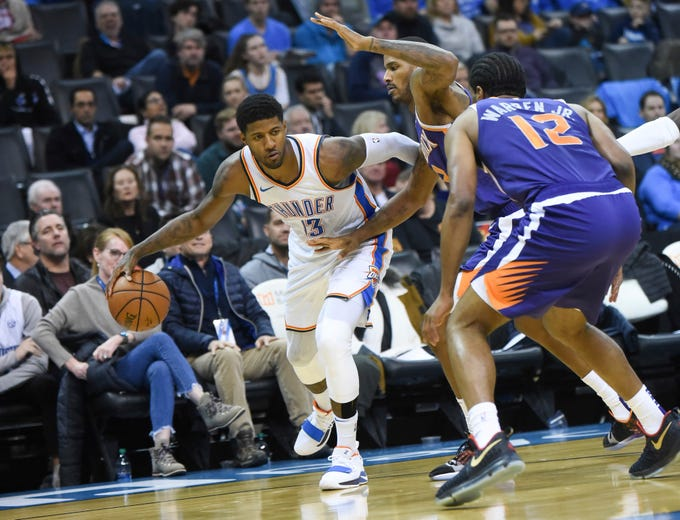 Oklahoma City Thunder forward Paul George (13) tries to push past Phoenix Suns forward Trevor Ariza (3) and T.J. Warren (12) in the second half of an NBA basketball game in Oklahoma City, Monday, Nov. 12, 2018.
