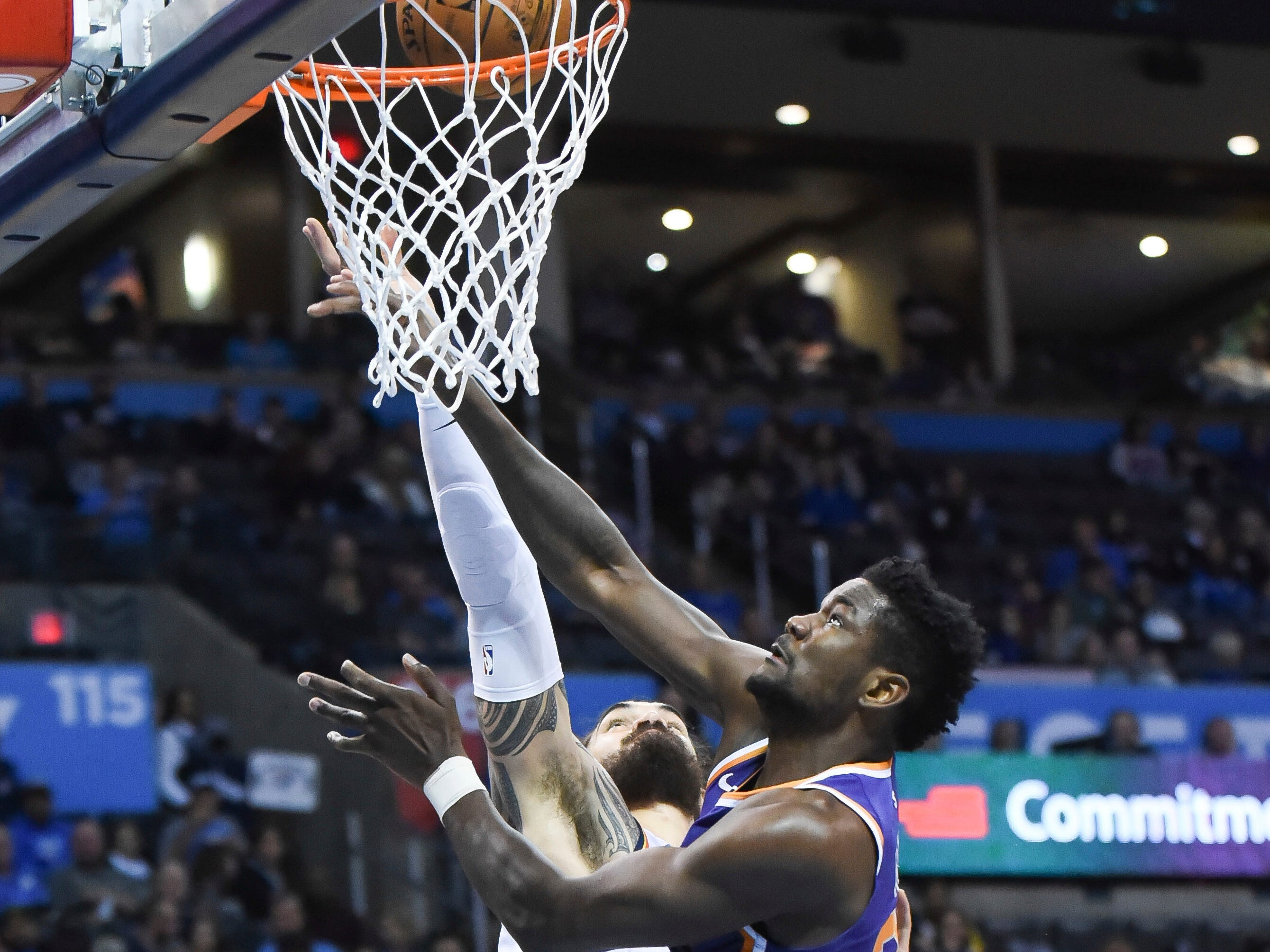 Oklahoma City Thunder center Steven Adams (12) tries to shoot the ball over Phoenix Suns center Deandre Ayton (22) in the second half of an NBA basketball game in Oklahoma City, Monday, Nov. 12, 2018.