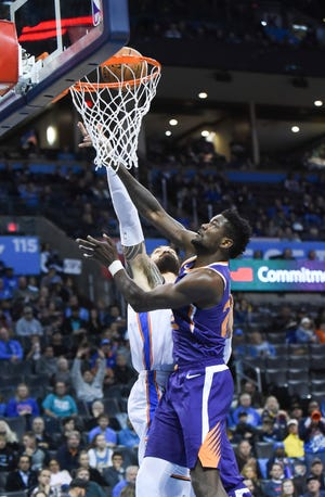 Oklahoma City Thunder center Steven Adams (12) tries to shoot the ball over Phoenix Suns center Deandre Ayton (22) in the second half of an NBA basketball game in Oklahoma City, Monday, Nov. 12, 2018.