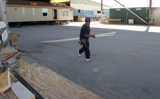 A Cavco Industries worker walks past an area at the company's mobile home factory on Nov. 18, 2010, in Phoenix.