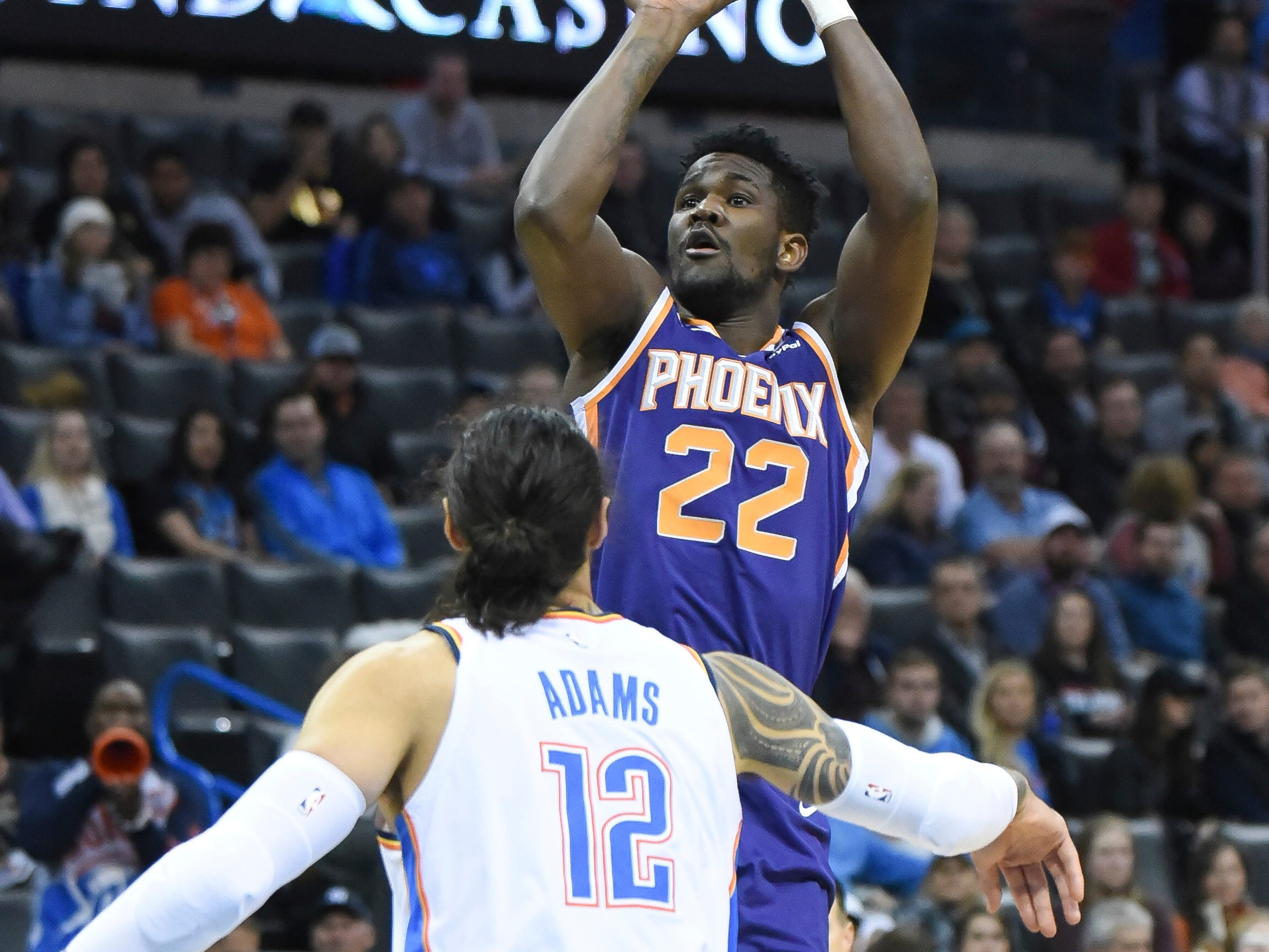 Phoenix Suns center Deandre Ayton (22) shoots the ball over Oklahoma City Thunder center Steven Adams (12) in the first half of an NBA basketball game in Oklahoma City, Monday, Nov. 12, 2018. (AP Photo/Kyle Phillips)