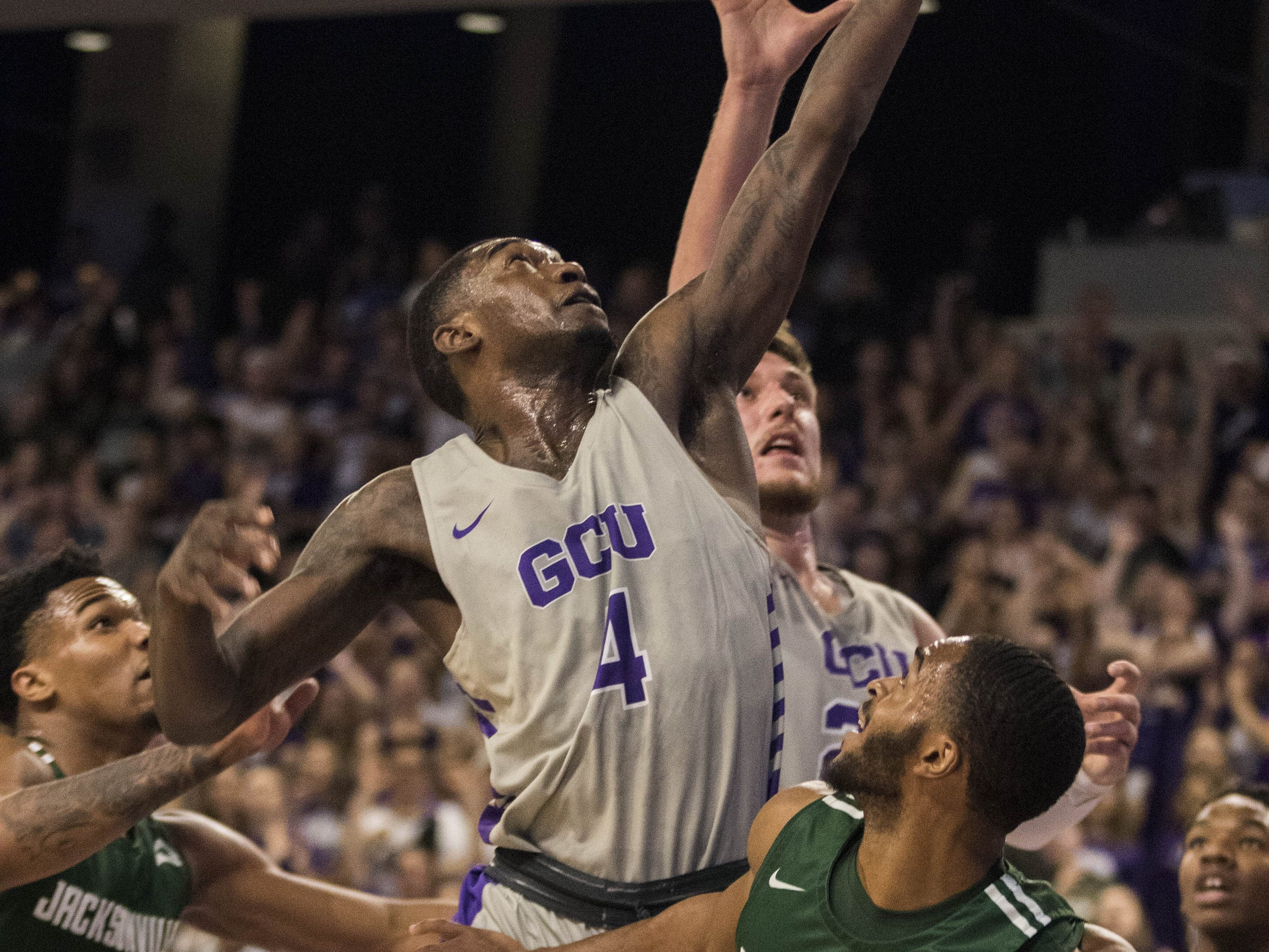 Grand Canyon University's Oscar Frayer (4) pulls down a rebound against Jacksonville's Tyreese Davis (23) and Aamahne Santos (10) during the first half of their game in Phoenix, Monday, Nov. 11, 2018.