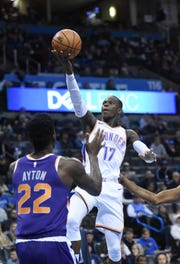 Oklahoma City Thunder guard Dennis Schroder (17) goes up for a shot over Phoenix Suns center Deandre Ayton (22) in the second half of an NBA basketball game in Oklahoma City, Monday, Nov. 12, 2018.