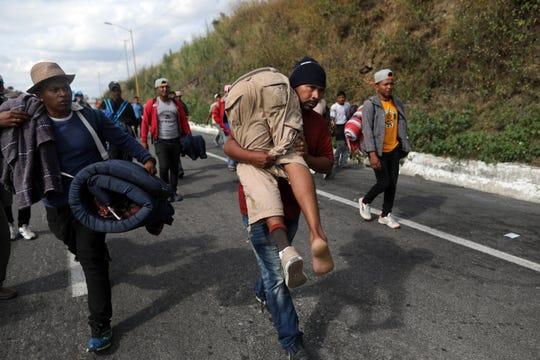 El migrante centroamericano Darwin Leonel Cárcamo camina con su compañero al hombro, luego que este se rompiera una pierna.