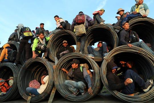 Migrantes centroamericanos se trepan sobre un tráiler para seguir su recorrido.