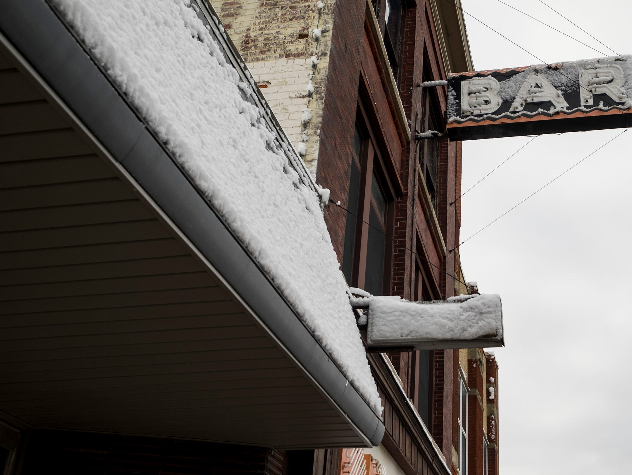 Snow is piled up on the sign of a downtown Port Huron storefront Tuesday, Nov. 13, 2018.