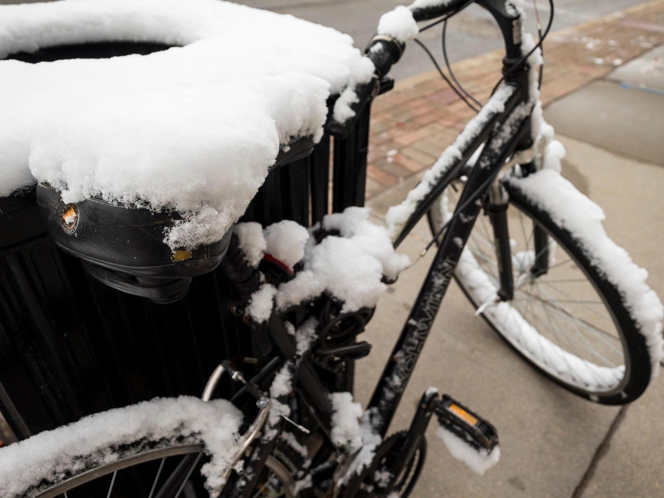 Snow covers the frame of a bicycle in downtown Port Huron.