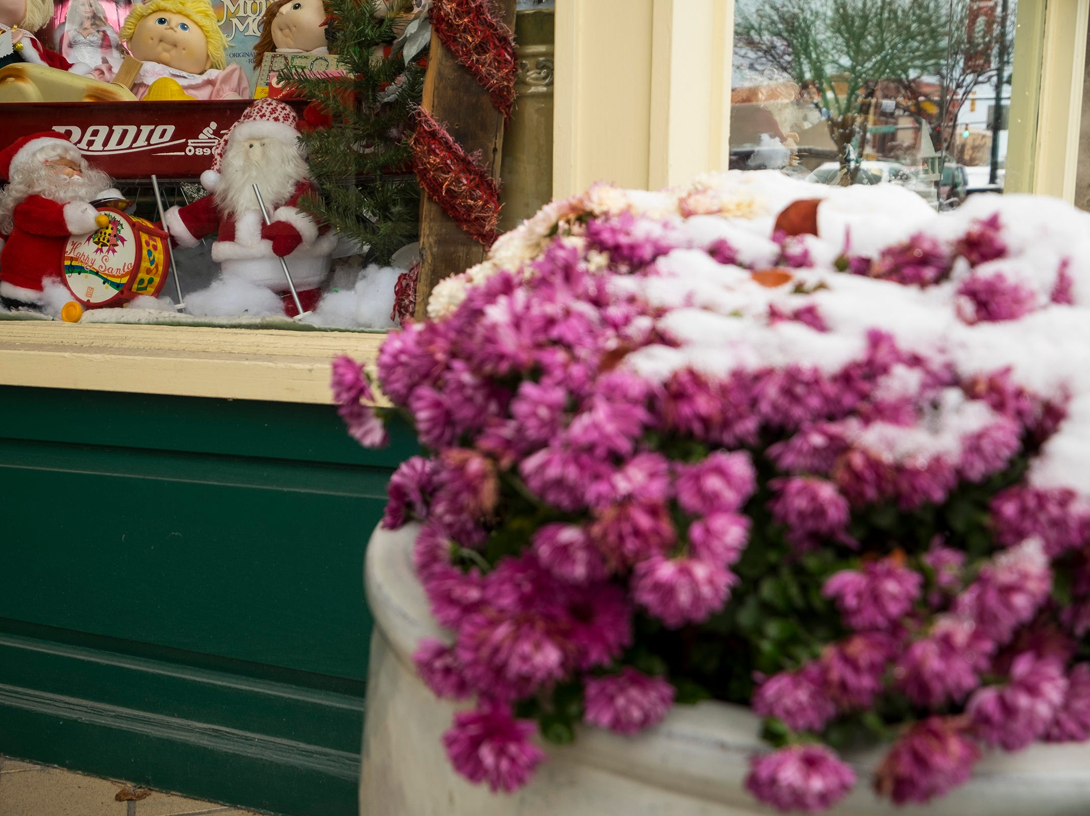 Santa Claus dolls stand in fake snow inside the window of a downtown Port Huron store Tuesday, Nov. 13, 2018.
