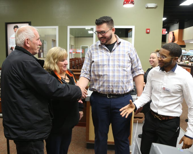 Two of the first customers of the day, Larry Curry and Dolly Matula, of Poughkeepsie, are welcomed by Bill Taylor, director of training and quality assurance and managing partner Lerone James at Golden Corral in the Town of Poughkeepsie on November 13, 2018.
