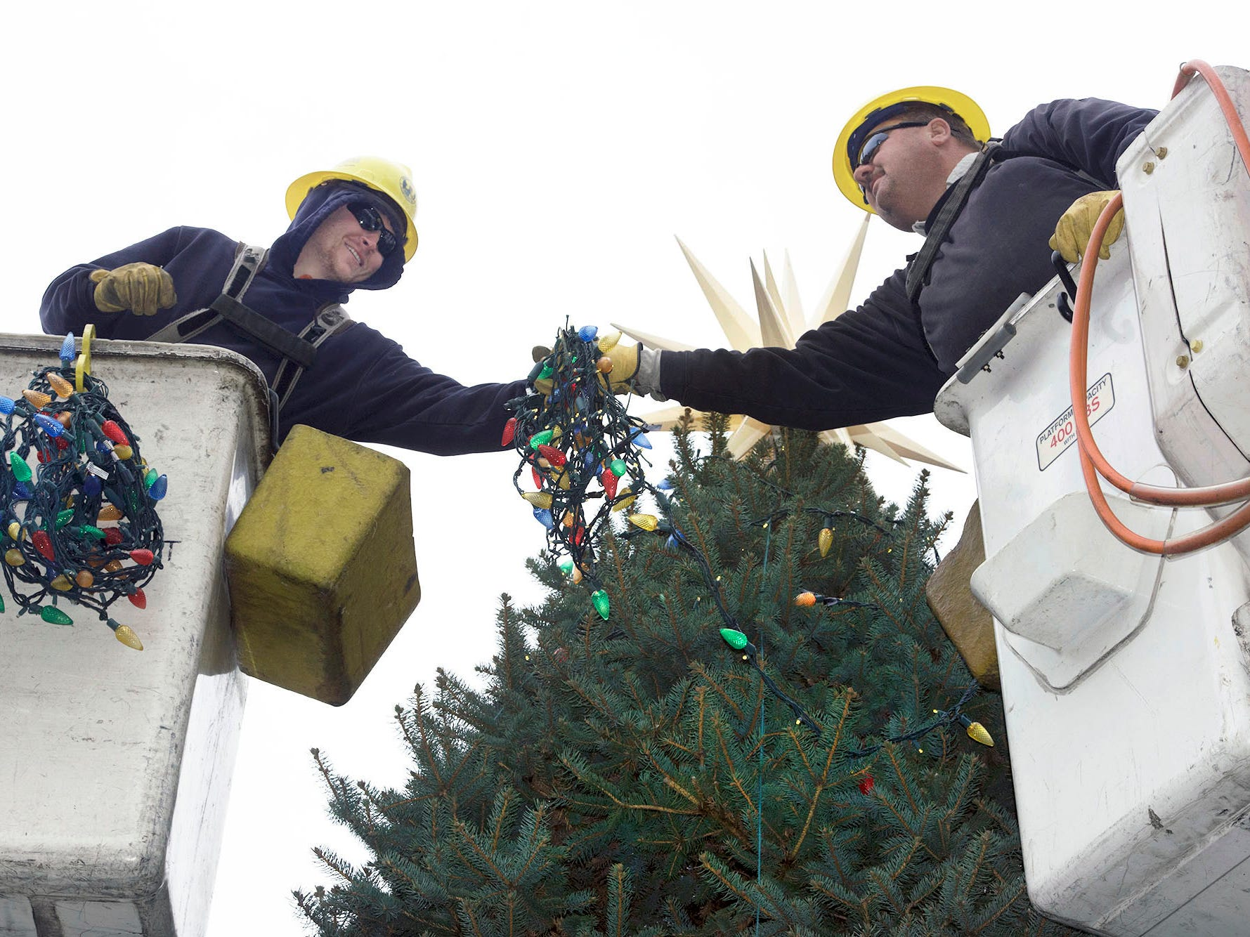 Borough of Chambersburg lineman Josh Swartz and Rob Roberts string lights on the Christmas tree at Memorial Square on Tuesday, November 13, 2018. This year's tree was donated by Darlene Fowler of Fayetteville.