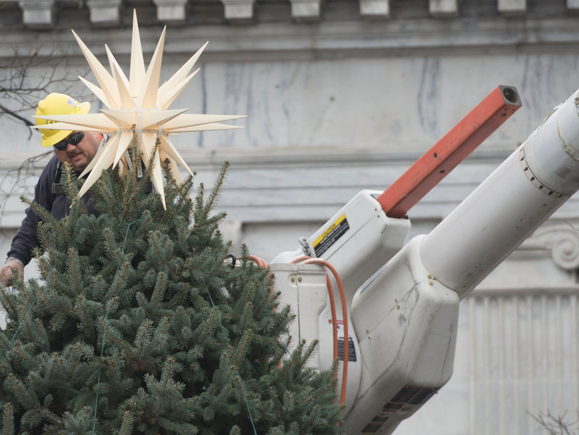 Borough of Chambersburg lineman Rob Roberts adjusts a star on top of the Christmas tree at Memorial Square on Tuesday, November 13, 2018. This year's tree was donated by Darlene Fowler of Fayetteville.