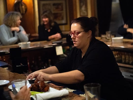 Carmen Durkin delivers wings to hungry customers at Roosevelt Tavern.