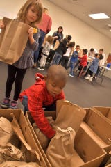 York Day Nursery children help pack 1,400 pounds of potatoes for a York Giving event.