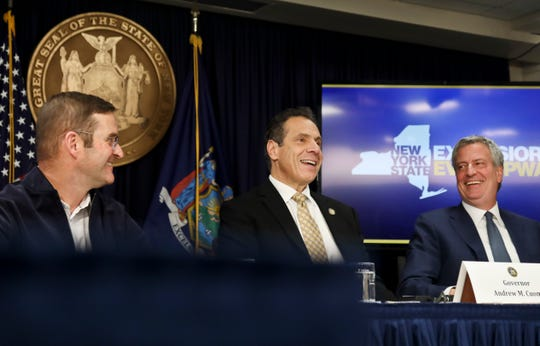 John Schoettler, Amazon vice president for real estate and facilities, left, joins New York Gov. Andrew Cuomo, center, and New York City Mayor Bill de Blasio during a news conference Tuesday Nov. 13, 2018, in New York.  (AP Photo/Bebeto Matthews)