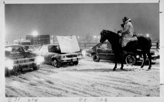 A Rochester mounted police officer assists stranded motorists during a snowstorm in December 1977.