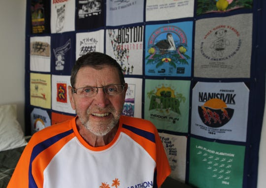 Norm Frank in his room at Legacy at Clover Blossom in Brighton in 2010. Behind Frank is a large quilt made up of T-shirts Frank received from the hundreds of marathons he has run in.
