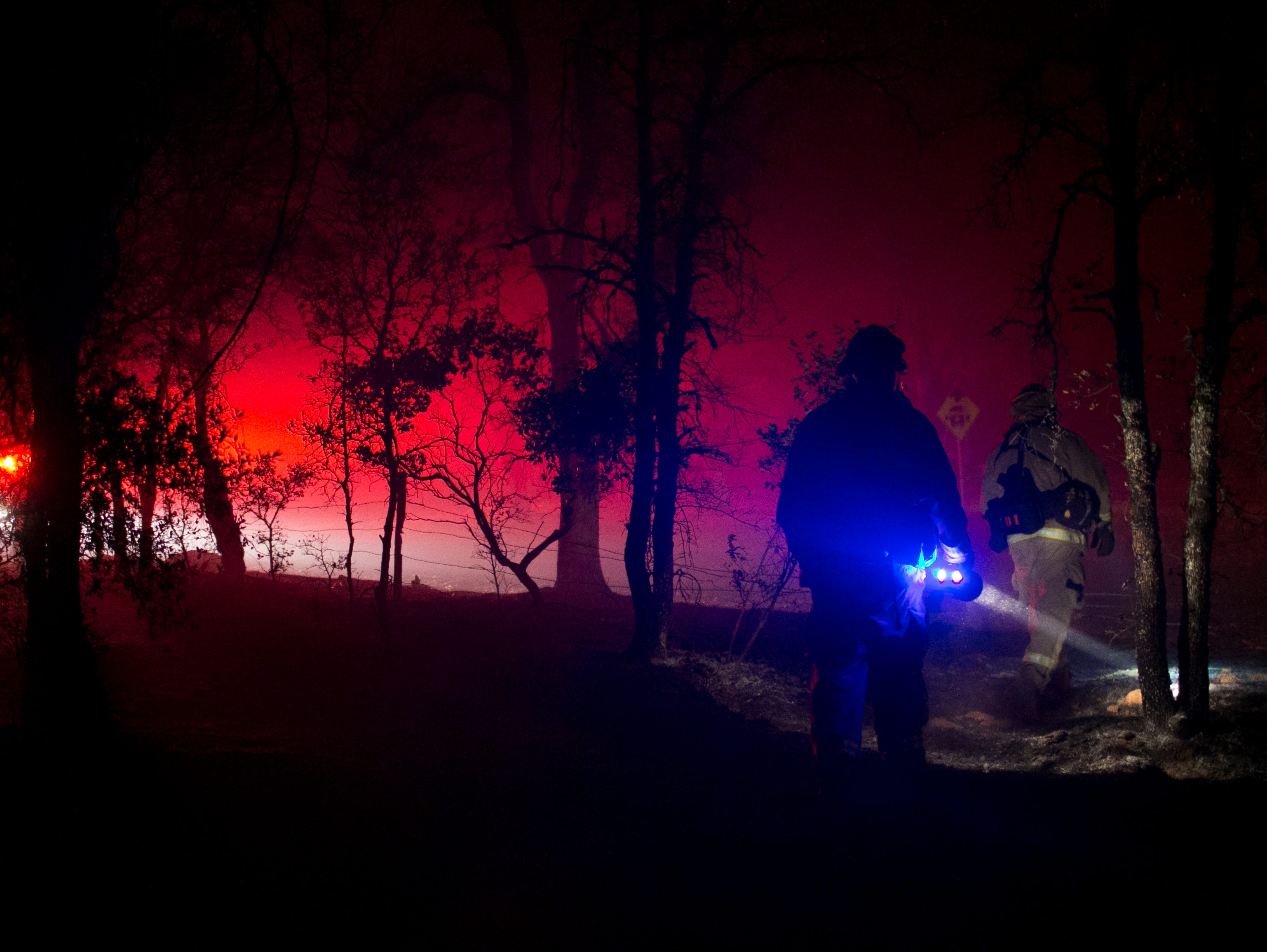 Firemen walk through a dark forest with headlamps looking for hot spots during the Camp Fire on Nov. 12, in Butte Valley, Calif.