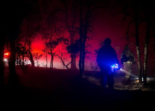 Firefighters walk through a dark forest with headlamps looking for hot spots during the Camp Fire on Nov. 12, 2018 in Butte Valley.