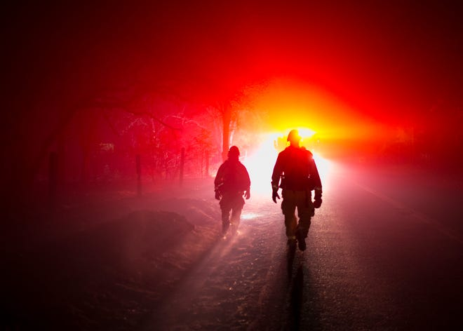 Firemen return to their truck during a night shift protecting homes and property from the Camp Fire on Nov. 12, in Butte Valley, Calif.