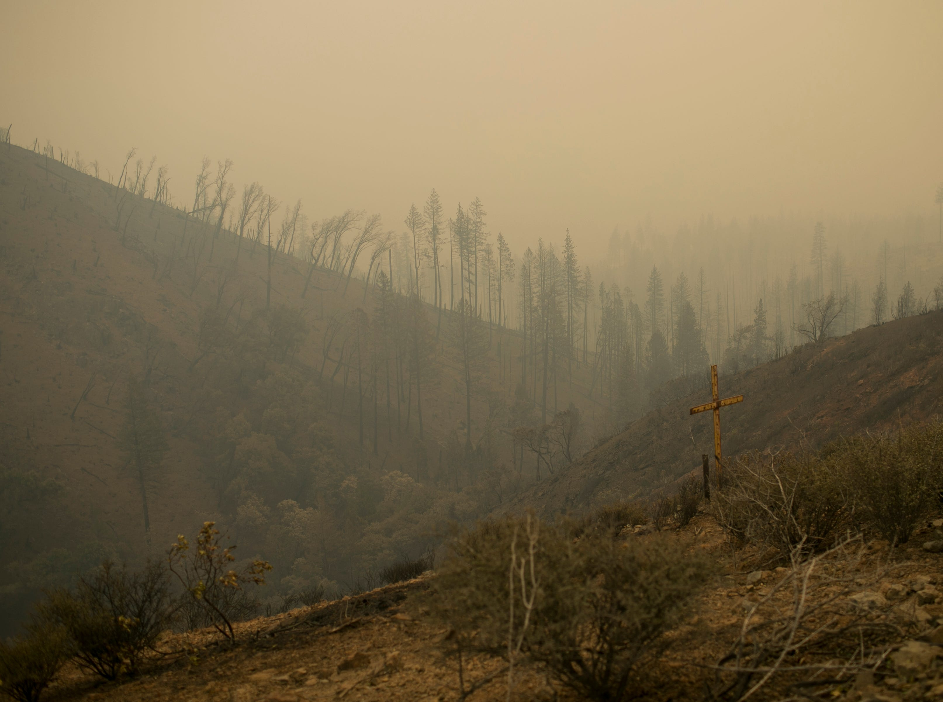 A cross looks over a valley filled with smoke from the Camp Fire on Nov. 12, in Butte Valley, Calif.