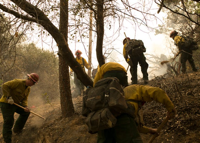 Firefighters work off of Highway 70 near the Camp Fire on Nov. 12, in Butte Valley, Calif.