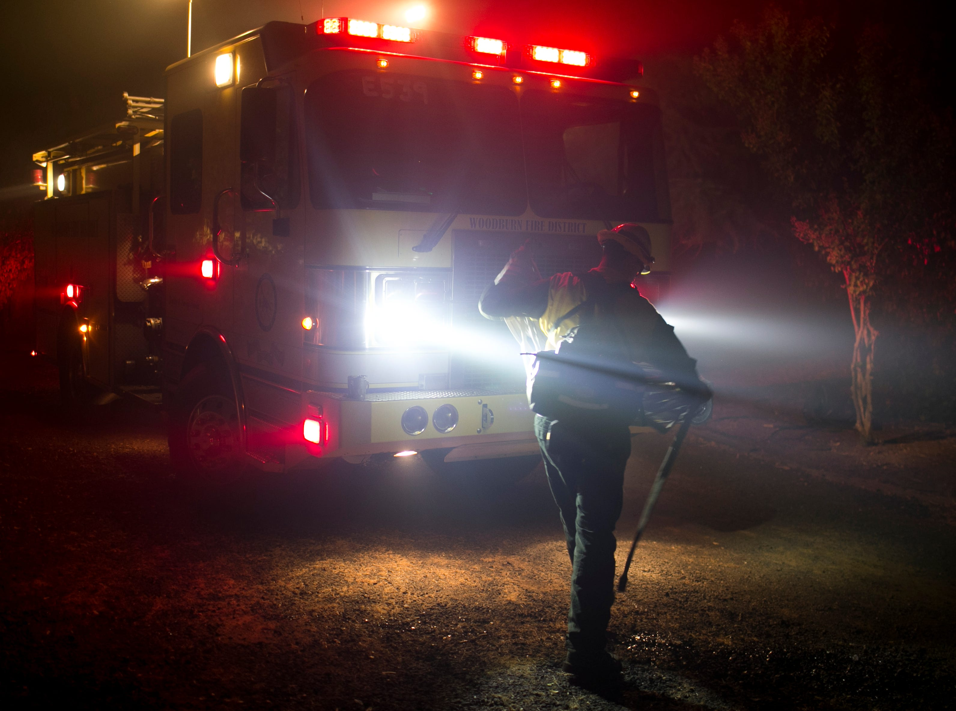 A fireman coils a firehose after helping put out a small fire during the Camp Fire on Nov. 12, in Butte Valley, Calif.