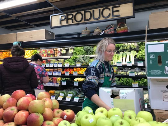 Produce Manager Rachel Saum restocks the shelves in her section at The Co-Op Natural Foods in Sioux Falls.
