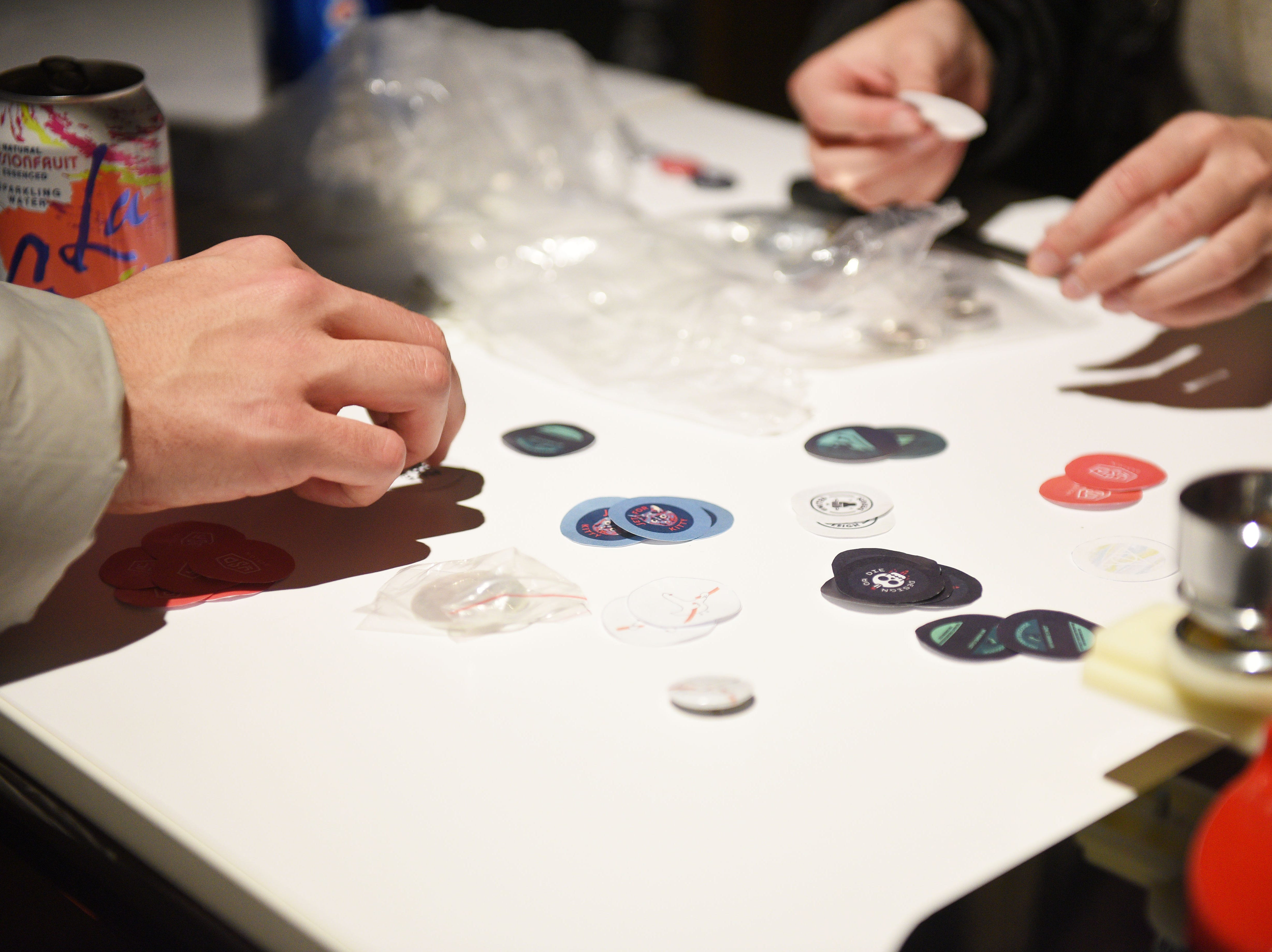 Attendees makes buttons during the USD Graphic Design Student work show Wednesday, Nov. 7, at the Sioux Falls Design Center in downtown Sioux Falls. Sherry He, not pictured, brought the button maker to the show as an activity for attendees.