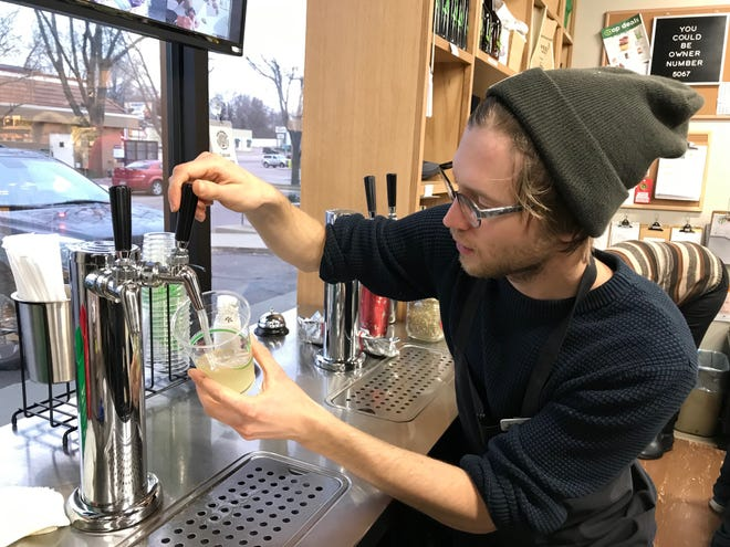 Jacob Fokken fills a glass with kombucha at The Co-Op Natural Foods in Sioux Falls. Fokken works in the produce section but recently began producing the store's kombucha, which is growing in popularity.