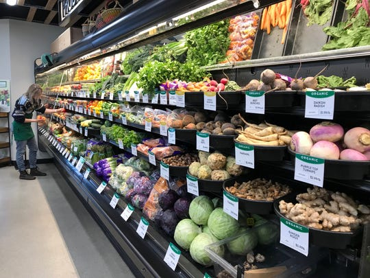 Rachel Saum, produce manager at The Co-Op Natural Foods in Sioux Falls, stocks her shelves with fresh produce.