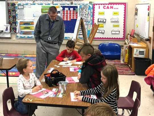 Kris Losh works with students in Mrs. Shiflet's kindergarten class at Guy K. Stump Elementary School. Losh is a reading aide at the school.