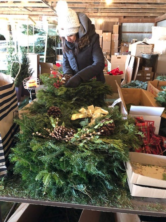 Employees at Hinkemeyer Tree Farm prepare fresh holiday wreaths in anticipation of their opening weekend.