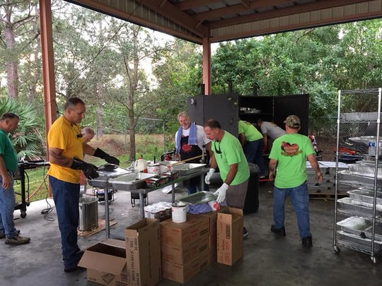 Firefighters and former Chief Ron Parrish prepare food for last year's Thanksgiving Day deliveries.
