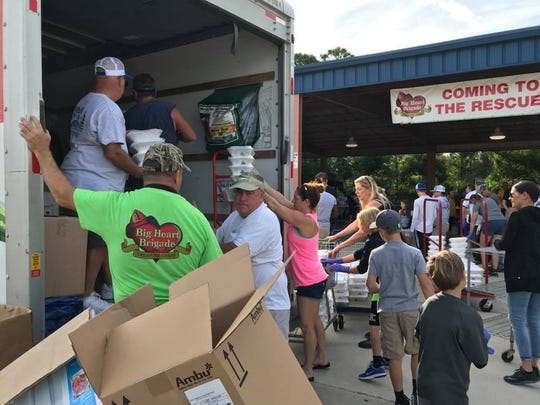 Volunteers and firefighters loading a truck with meals during last year's project.