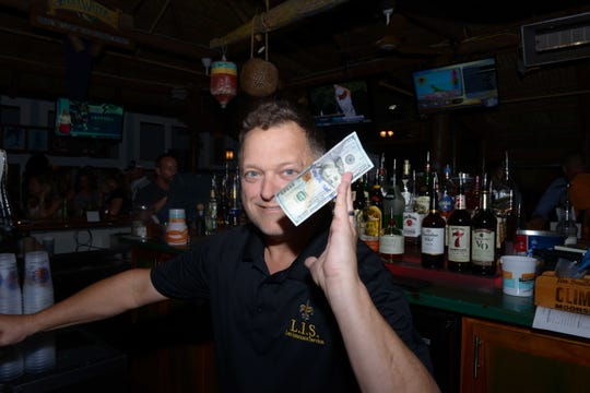 Frankie Lott gets a big tip at Family Meals' fourth annual Celebrity Bartender's Event at Cobb's Landing in Fort Pierce.
