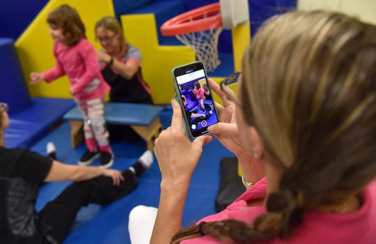 Lisa Jones (right), adoptive mother of Maci Jones, 3, records video of Maci as she takes her first steps alone with leg braces, under the guidance of physical therapy technician Brianna Pesce (far left) and physical therapy assistant Erica Pechart, at Sunshine Physical Therapy Center on Tuesday, Nov. 13, 2018, in Vero Beach.