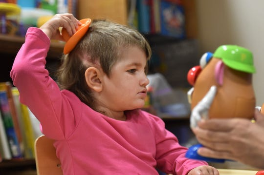 "Maci Jones, 3, tries on a hat for the Mr. Potato head toy she is constructing as Heather Moxley (out of the picture), speech therapy assistant, holds her version, as the two work together during Maci's speech therapy session on Tuesday, Nov. 13, 2018, at Sunshine Physical Therapy Center in Vero Beach. ""She has made improvements, she's doing really well,"" Moxley said."
