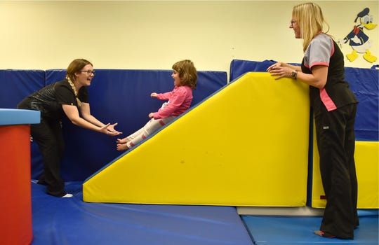 """Physical therapy technician Brianna Pesce (left) and physical therapy assistant Erica Pechart help Maci Jones, 3, with her physical therapy session at at Sunshine Physical Therapy Center on Tuesday, Nov. 13, 2018, in Vero Beach. """"She's doing great, she's made a ton of progress,"""""""