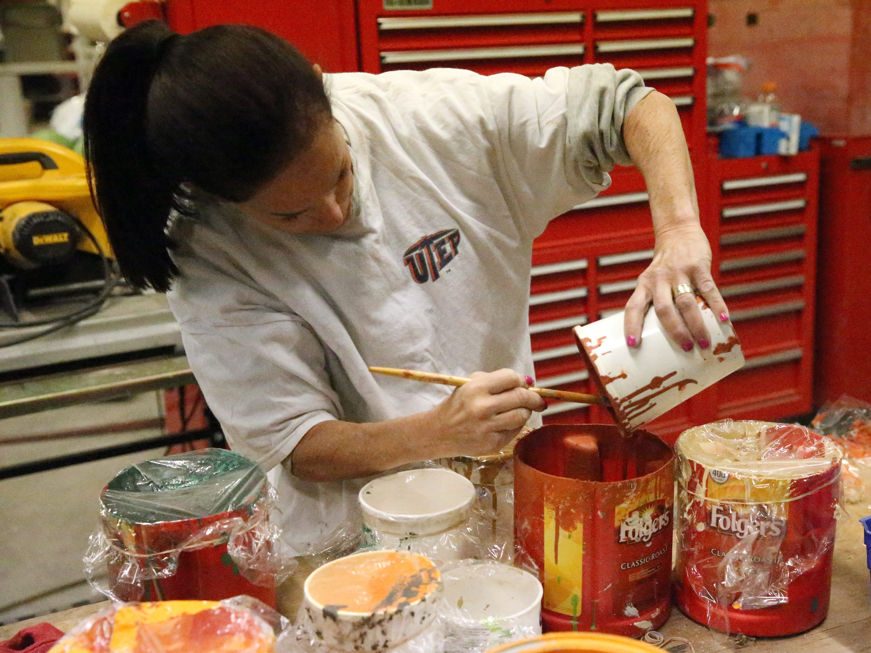 Robin Kobren, a parade float volunteer pours paint while working on a parade float Monday.