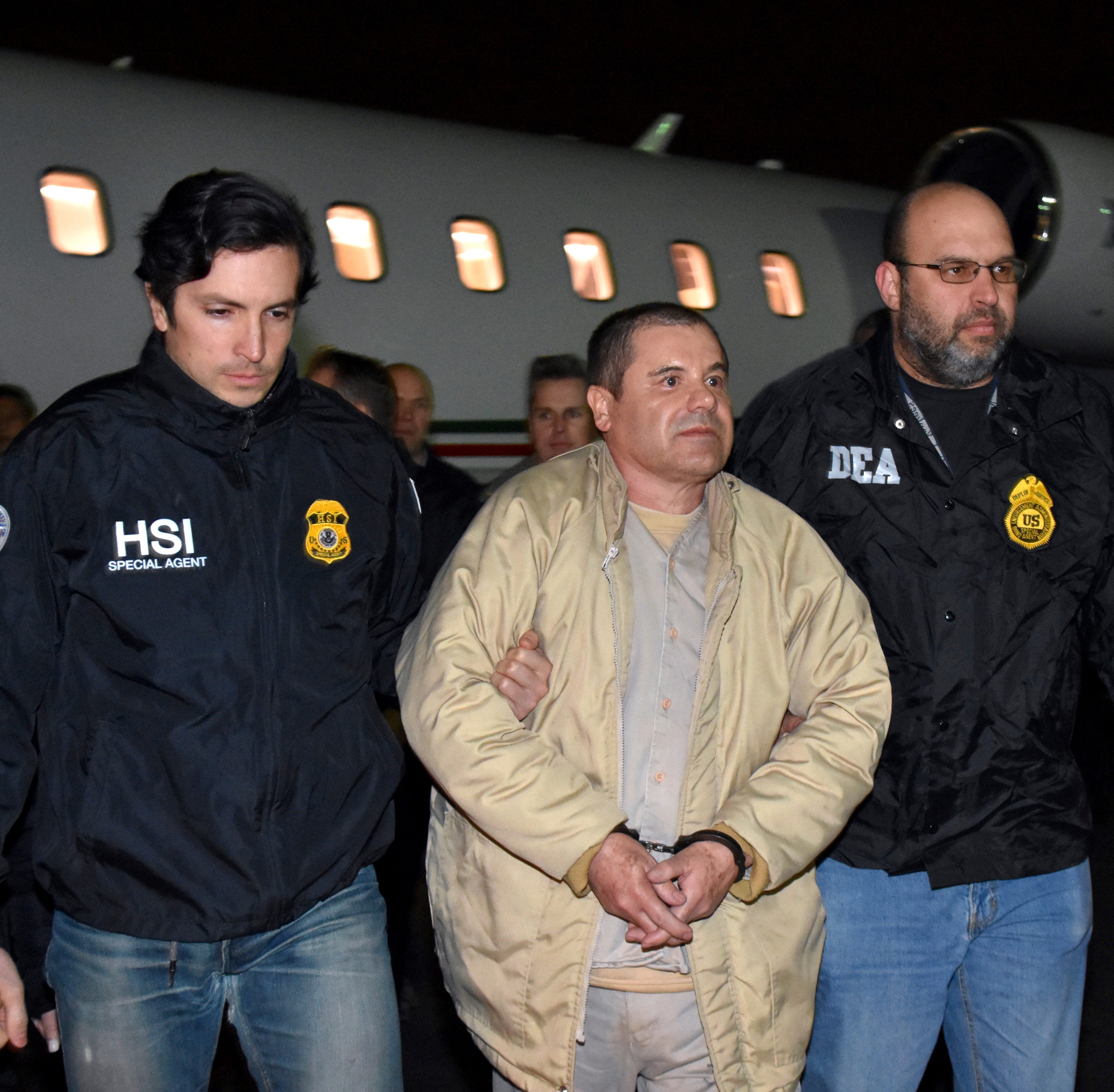 "In this Jan. 19, 2017, file photo provided U.S. law enforcement, authorities escort Joaquin ""El Chapo"" Guzman, center, from a plane to a waiting caravan of SUVs at Long Island MacArthur Airport in Ronkonkoma, N.Y. A jury has been picked for the U.S. trial of the Mexican drug lord. Seven women and five men were selected Nov. 7, 2018, as jurors in the case against Guzman. The trial is set to begin Tuesday, Nov. Nov. 13, 2018, with opening statements in federal court in Brooklyn."