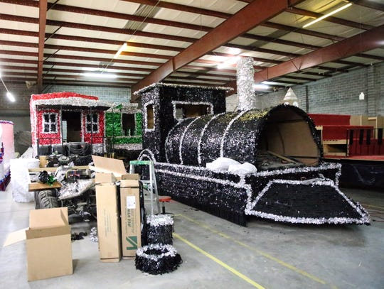 A multiunit train float is being readied for the FirstLight Federal Credit Union Sun Bowl Parade on Thanksgiving Day. The engine is fitted over an eight-cylinder SUV.