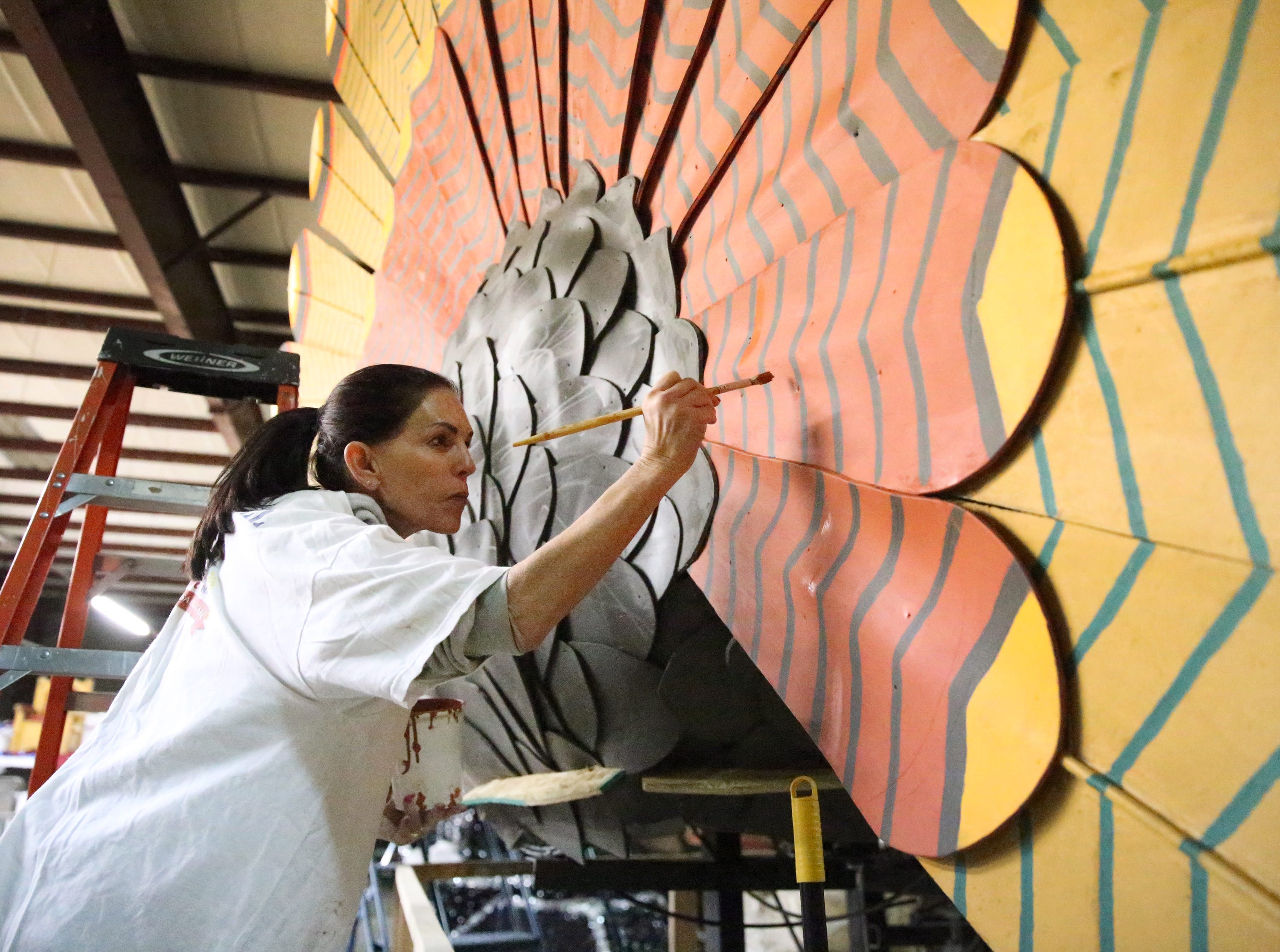 Robin Kobren paints a large turkey on the lead float for FirstLight Federal Credit Union.