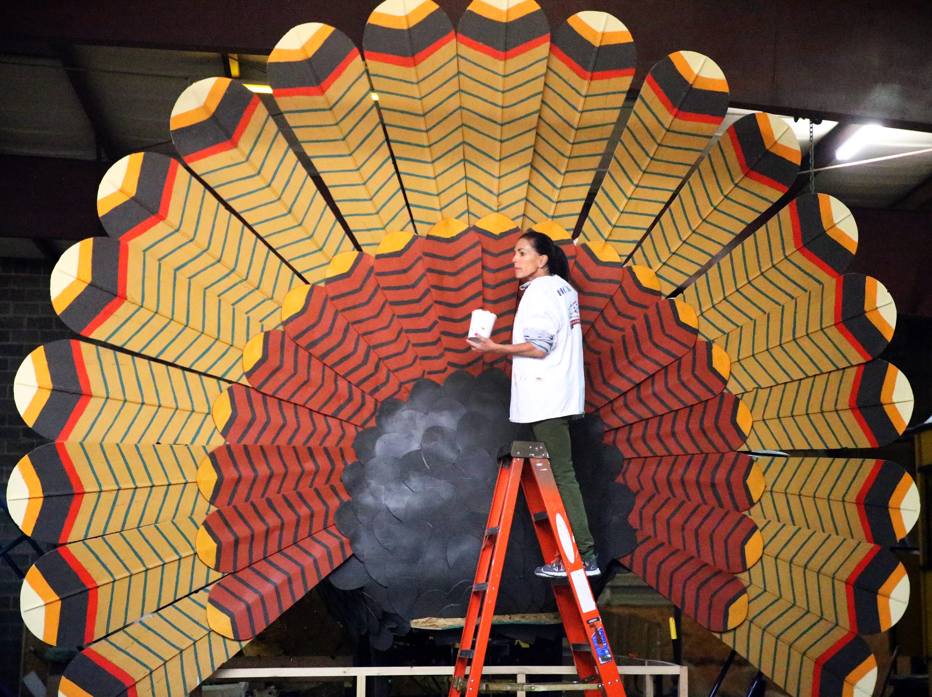Robin Kobren, a parade float volunteer paints the back side of a giant turkey parade float for First Light Federal Credit Union, title sponsor of the 82bd annual Sun Bowl Parade inside a warehouse in East-Central El Paso Monday.